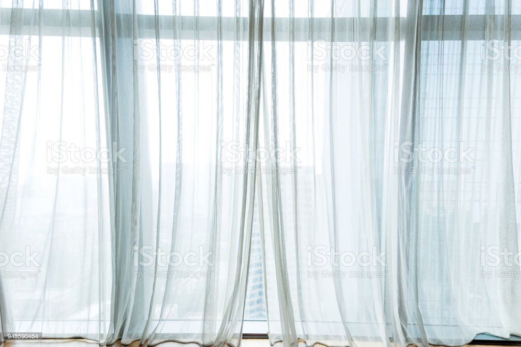 White curtain hanging in the window stock photo