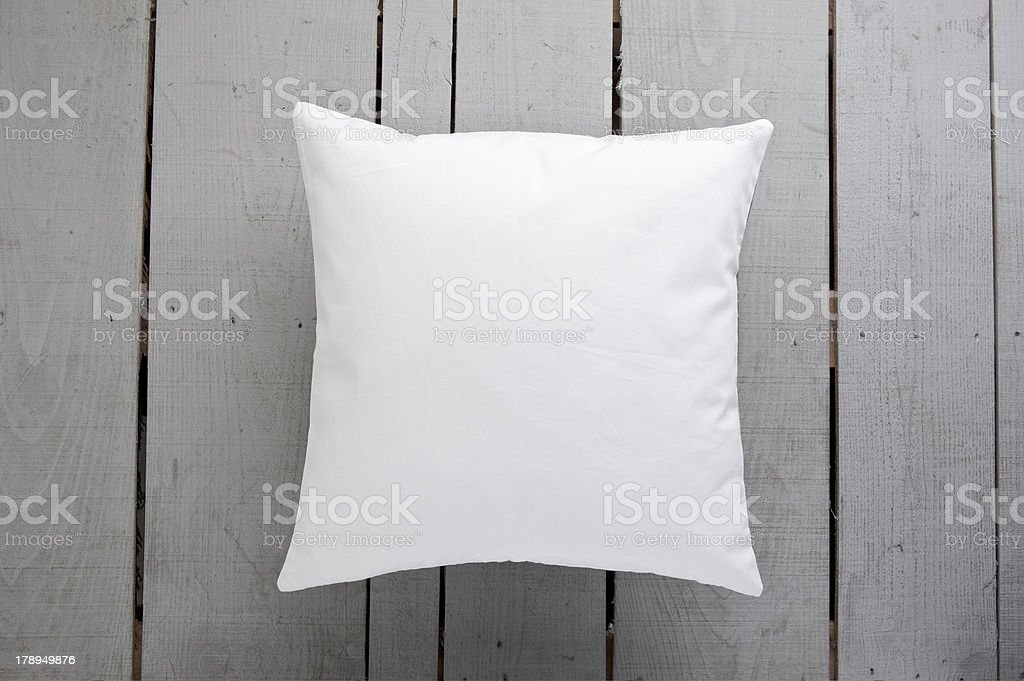 White cushion on wooden background stock photo