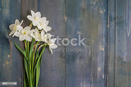 White daffodils on a rustic wooden background with copy space in a flat lay composition