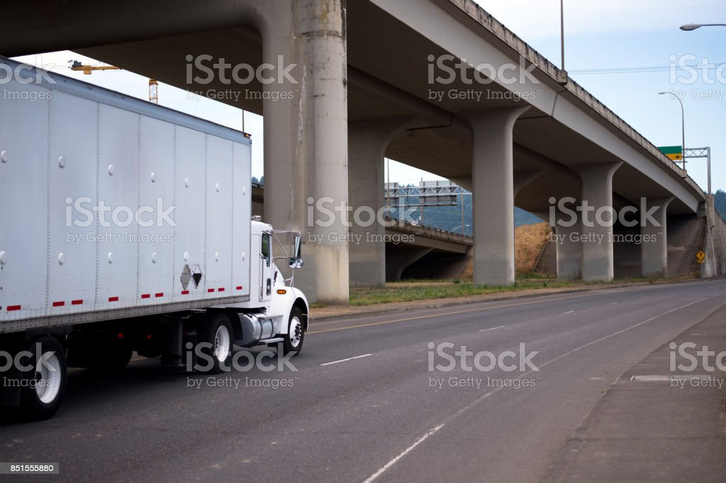 White day cab semi truck with box trailer running on the road under overpass  trestle stock photo