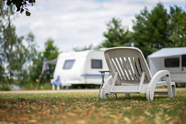 White deckchair in a meadow at a campsite stock photo