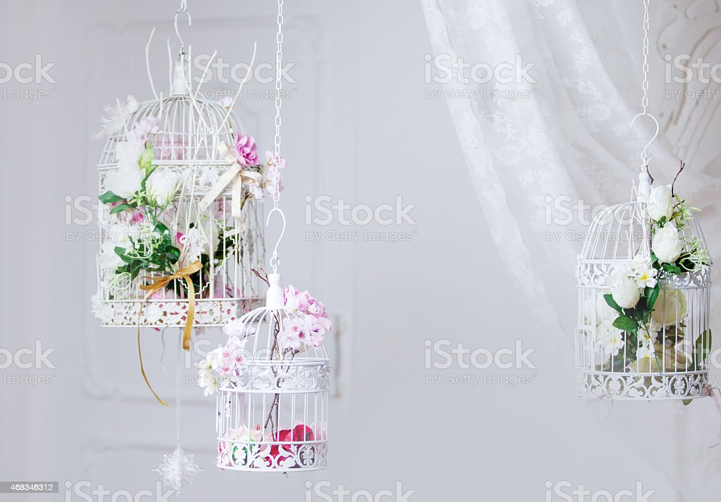 White decorative cage with beautiful flowers, suspension cells royalty-free stock photo