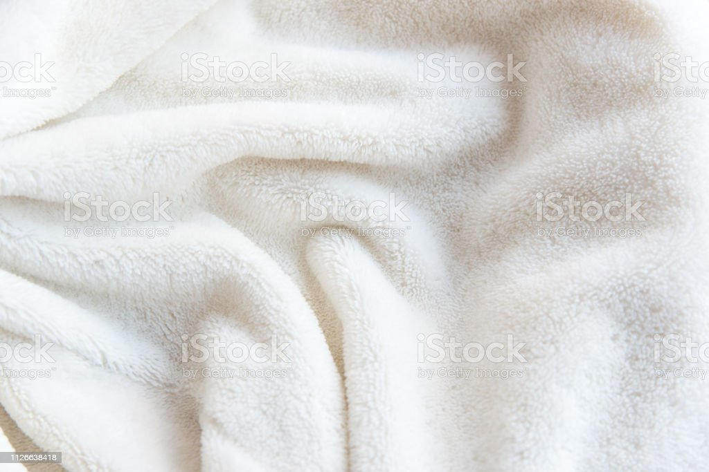 White delicate soft background of plush fabric. Texture of beige soft...