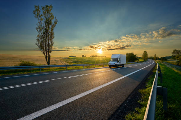 White delivery van driving on asphalt road around farm fields in rural landscape at sunset White delivery van driving on asphalt road around farm fields in rural landscape at sunset commercial land vehicle stock pictures, royalty-free photos & images