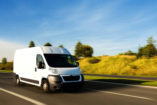 White delivery van on the road A van speeding on the highway commercial land vehicle stock pictures, royalty-free photos & images