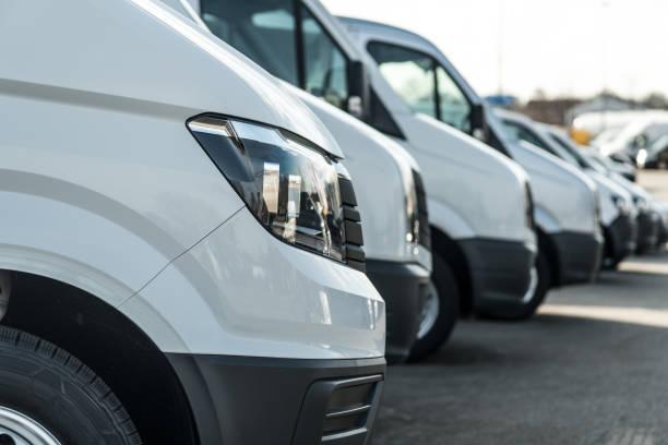 weißer lieferwagen - fokus auf den ersten scheinwerfer - autotransporter stock-fotos und bilder