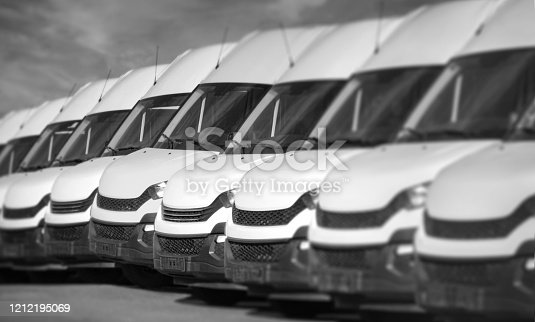 1140988145 istock photo White delivery vans in a row 1212195069