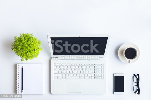 istock White desk office with laptop, smartphone and other supplies with cup of coffee. Top view with copy space for input the text. Designer workspace on desk top, view with essential elements on flat lay. 1001276344