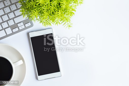 istock White desk office with laptop, smartphone and other supplies with cup of coffee. Top view with copy space for input the text. Designer workspace on desk top, view with essential elements on flat lay. 1005736150