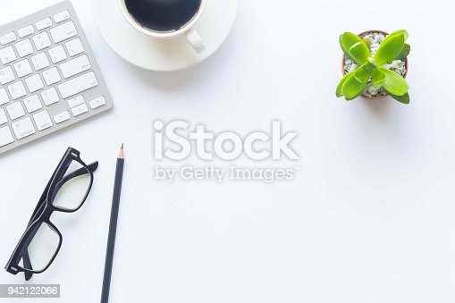 istock White desk office with laptop, smartphone and other supplies with cup of coffee. Top view with copy space for input the text. Designer workspace on desk top, view with essential elements on flat lay. 942122066