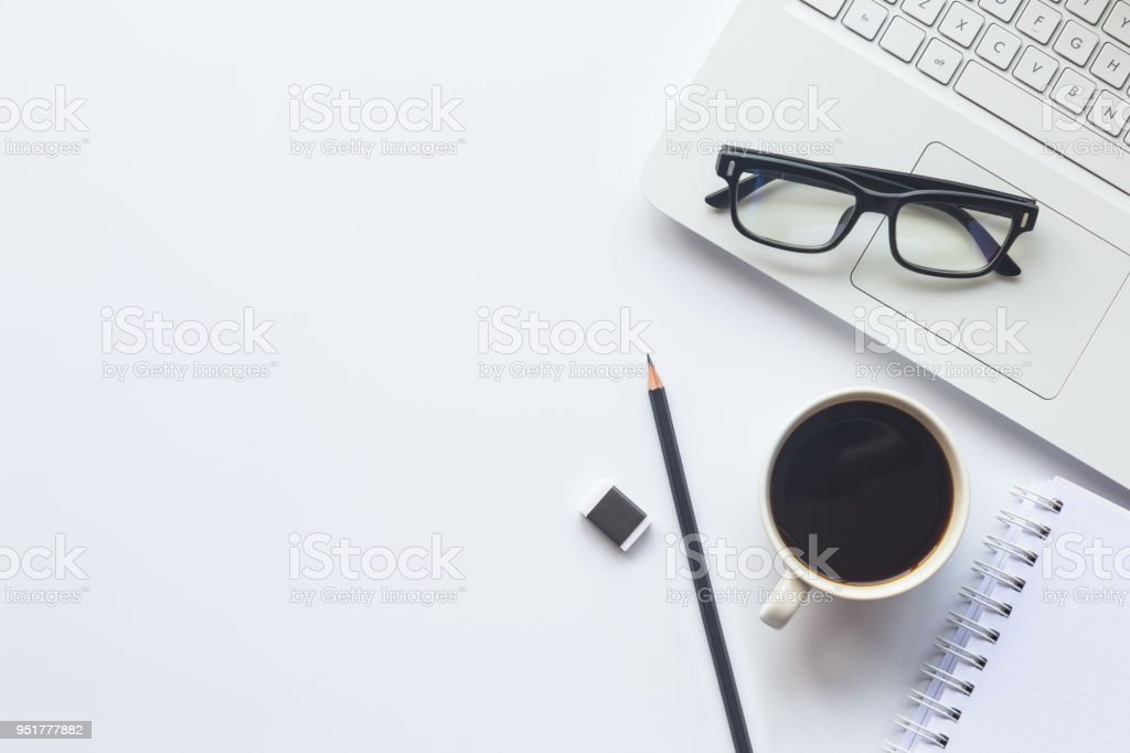 White desk office with laptop, smartphone and other supplies with cup of coffee. Top view with copy space for input the text. Designer workspace on desk top, view with essential elements on flat lay.