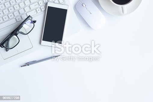 istock White desk office with laptop, smartphone and other supplies with cup of coffee. Top view with copy space for input the text. Designer workspace on desk top, view with essential elements on flat lay. 969927298