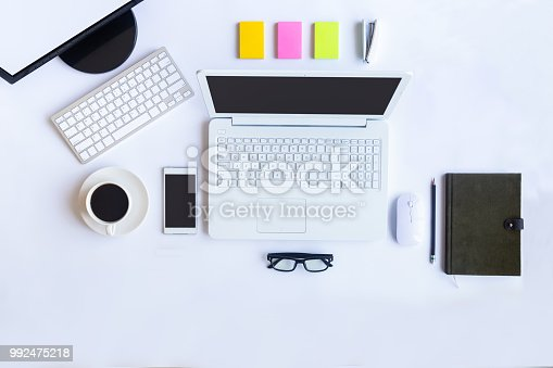 istock White desk office with laptop, smartphone and other supplies with cup of coffee. Top view with copy space for input the text. Designer workspace on desk top, view with essential elements on flat lay. 992475218