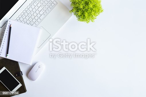 956234478 istock photo White desk office with laptop, smartphone and other supplies with cup of coffee. Top view with copy space for input the text. Designer workspace on desk top, view with essential elements on flat lay. 998101134