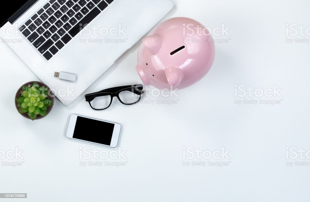 White desktop with piggy bank for finance concept stock photo