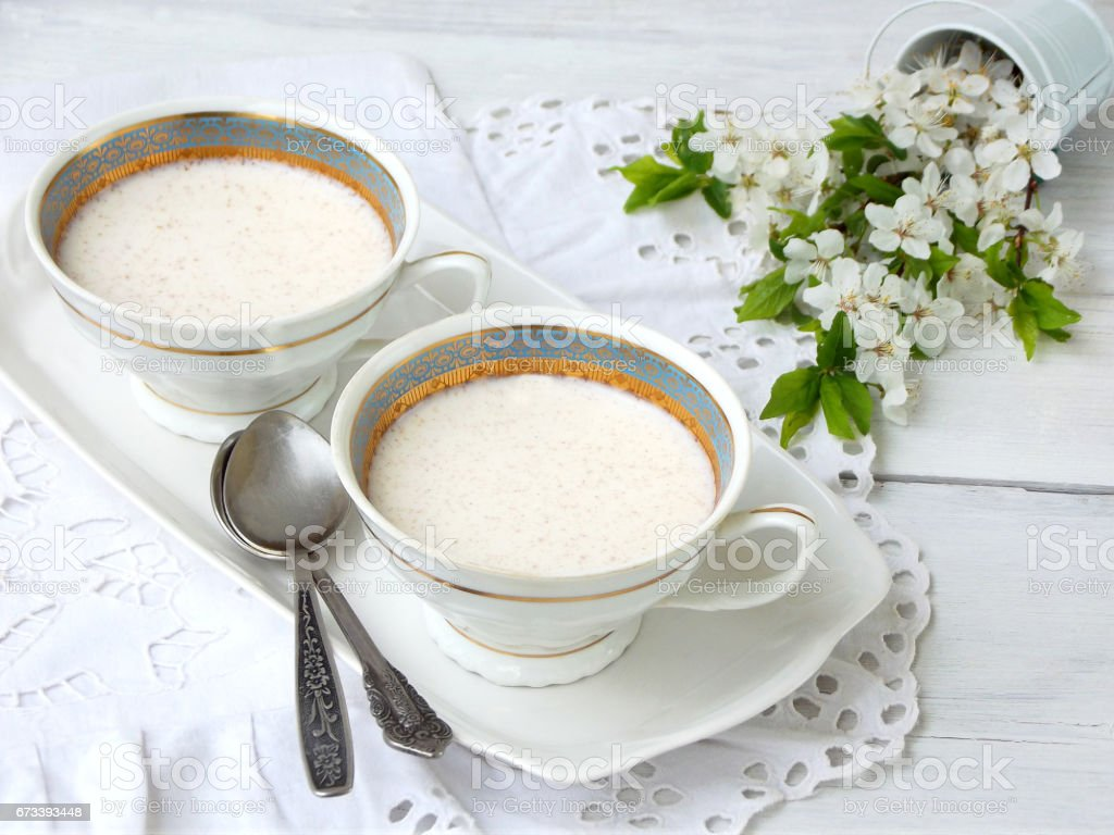 White dessert Junket from milk and rennet extract with cinnamon in cups on light background. Jelly-like pudding made from sweet cottage cheese. Healthy food. stock photo