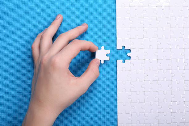 white details of a puzzle on a blue background. a puzzle is a pu - puzzles stock photos and pictures