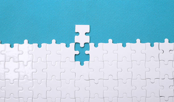 White details of a puzzle on green background. A puzzle is a puz stock photo