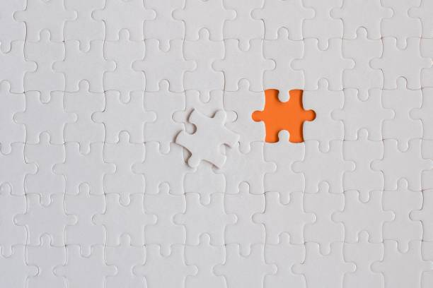 white details of jigsaw puzzle on orange background - incomplete stock pictures, royalty-free photos & images