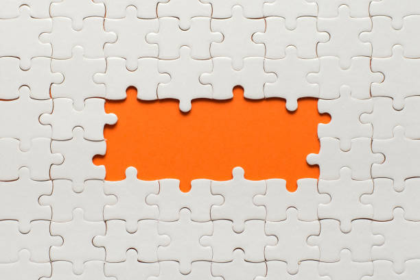White details of puzzle on orange background and place for inscription stock photo