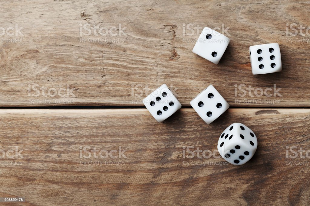White dice on wooden table. Gambling devices. Game chance concept. stock photo