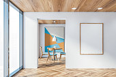 Interior of panoramic dining room with white walls, wooden floor, round table with blue chairs and abstract picture and vertical mock up poster frame. 3d rendering