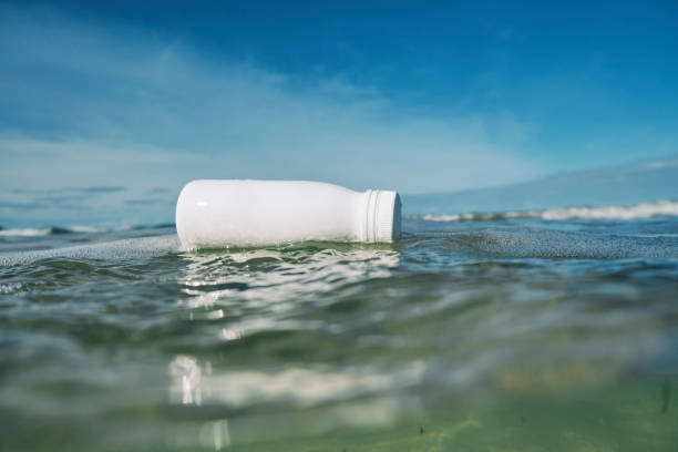 white discarded plastic bottle floating on the sea surface. - trash stock pictures, royalty-free photos & images