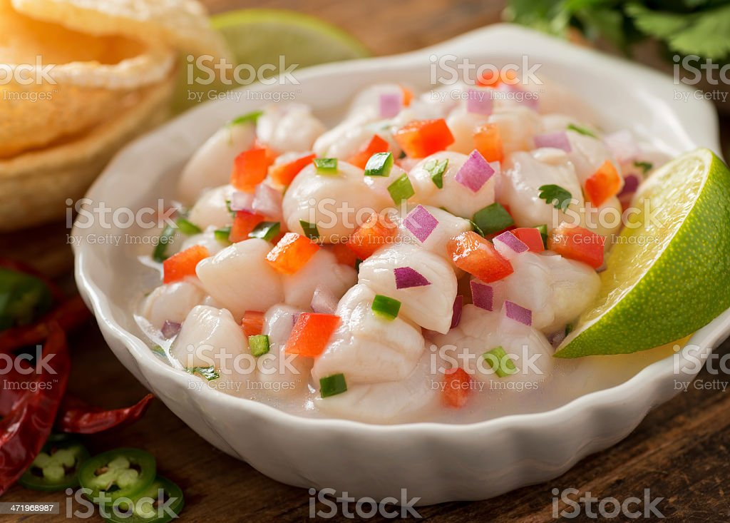 A white dish of ceviche garnished with a slice of lime stock photo