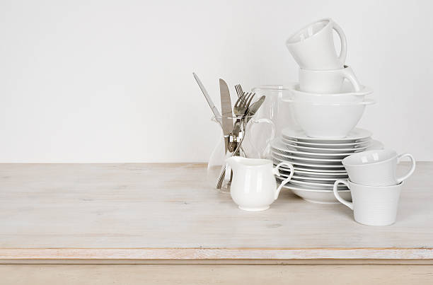 white dishware and cutlery on wooden table with copy space - modernes geschirr stock-fotos und bilder