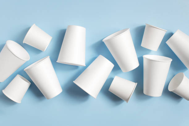 White disposable cups on the light blue background Various white disposable cups on the light blue background, top view disposable cup stock pictures, royalty-free photos & images