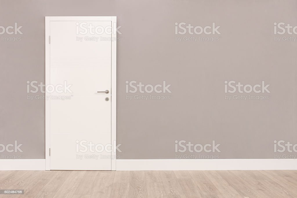 White door in an empty room stock photo
