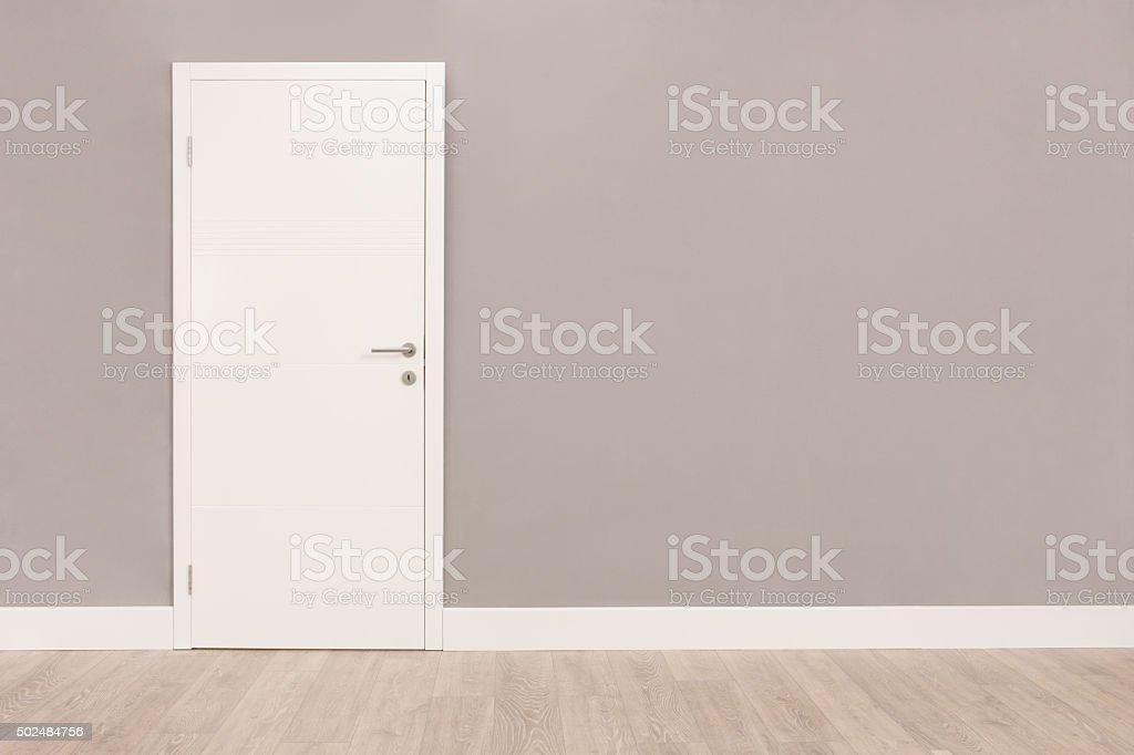 White door in an empty room stock photo