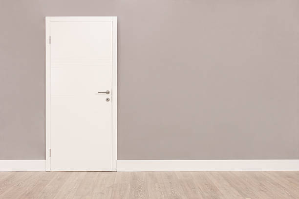 White door in an empty room Shot of a closed white door on a gray wall in an empty room doorway stock pictures, royalty-free photos & images