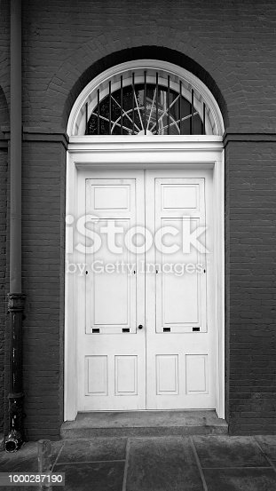 New Orleans, LA USA - May 9, 2018  -  White Door in Red Building in the French Quarter B&W