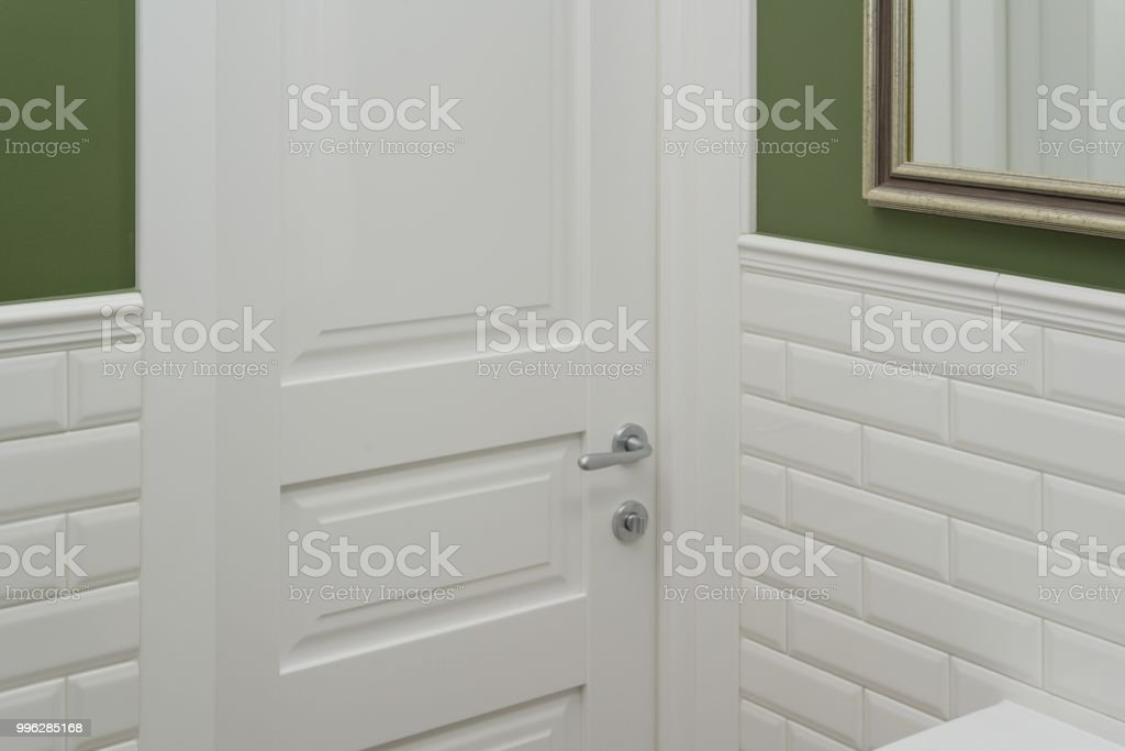 Picture of: White Door In The Bathroom Toilet Room Background Green Painted Wall Covered With Decorative Ceramic Tiles With White Glossy Bricks Interior Details Closeup Stock Photo Download Image Now Istock