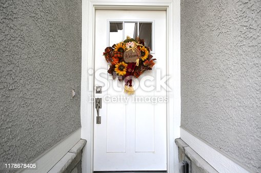 istock White Door with Autumn Wreath 1178678405