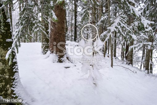 White dream catcher in the snowy forest