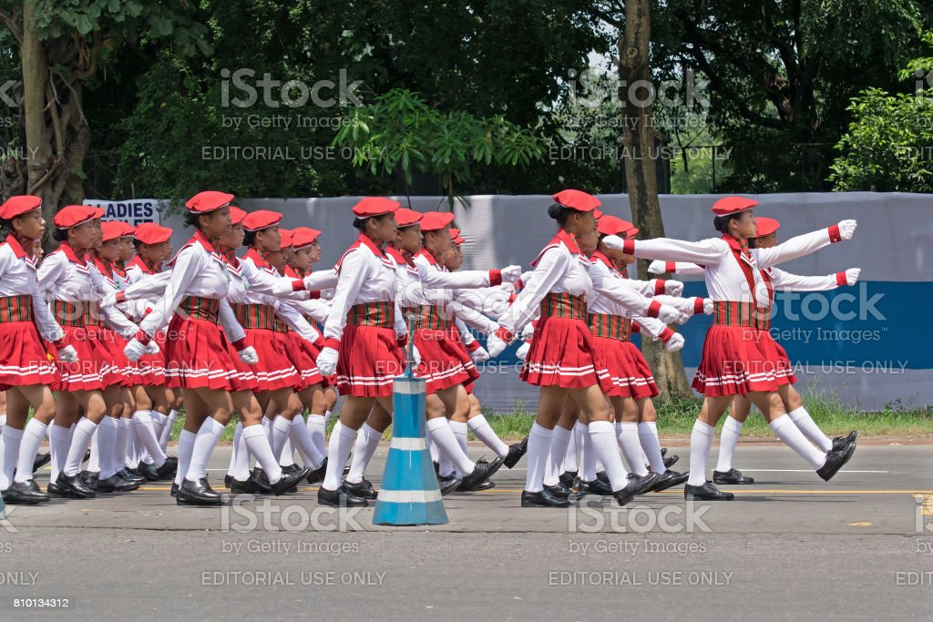 White dressed girls marching past on road. stock photo