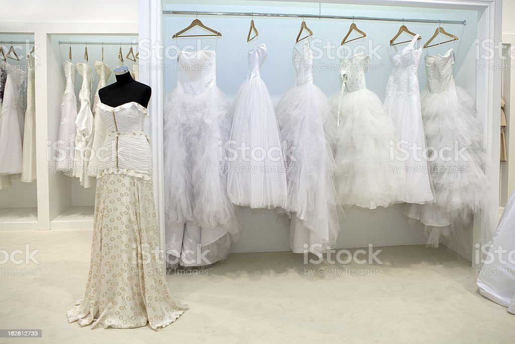 696c02f47a White dresses hanging from rack in bridal shop royalty-free stock photo