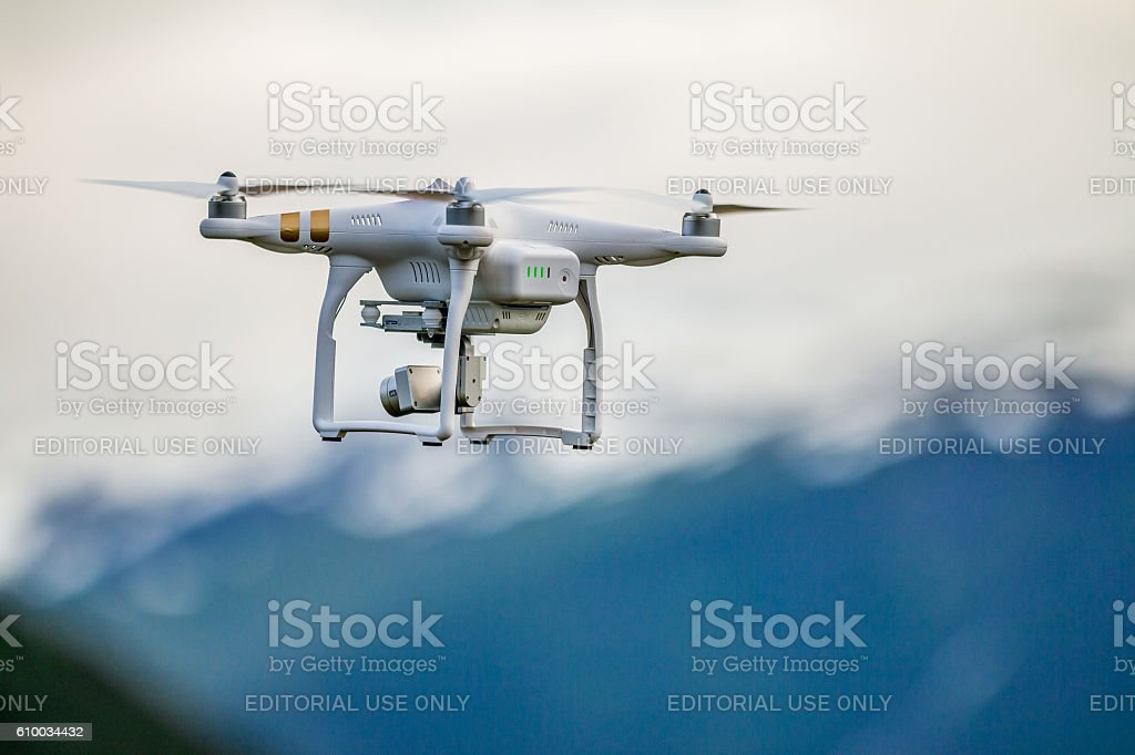 White drone flying above mountains. stock photo