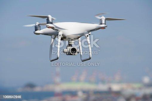 Kagawa, Japan - October 25, 2018: White drone with high resolution digital camera flying above the Tadotu-city, Kagawa. Take-off or landing quadcopter.