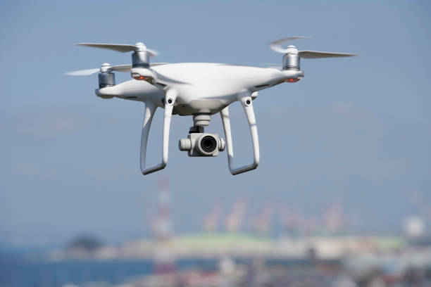 White drone flying over the city Kagawa, Japan - October 25, 2018: White drone with high resolution digital camera flying above the Tadotu-city, Kagawa. Take-off or landing quadcopter. drone point of view stock pictures, royalty-free photos & images