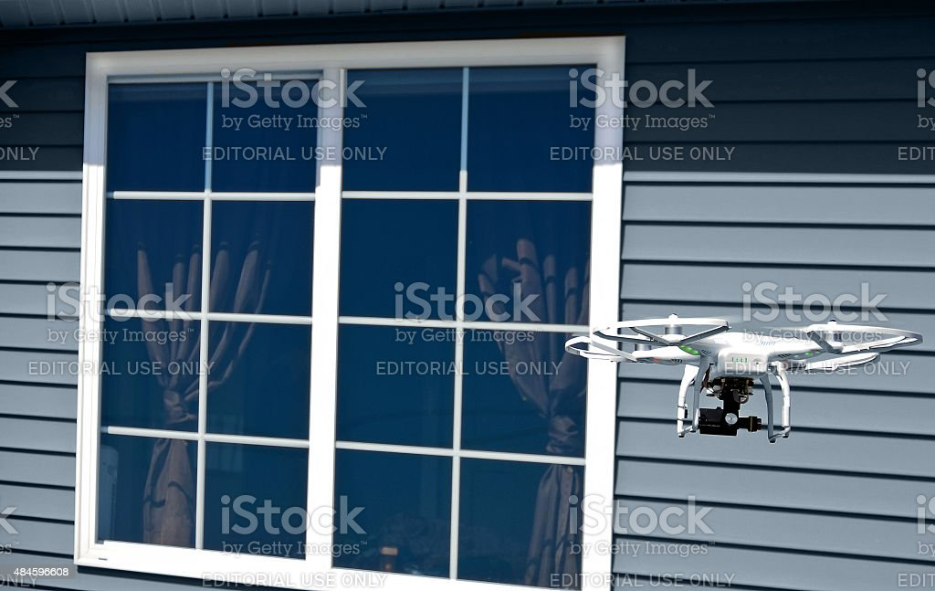 white drone with camera by house window stock photo