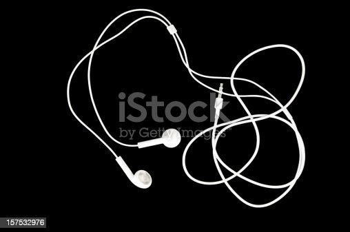Brilliant white earbuds on a black background with copy space.