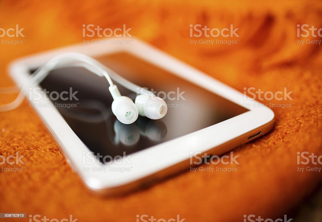 White earphones and tablet pc, close up photo, small dof stock photo