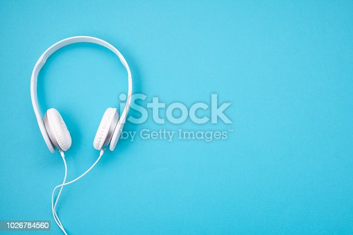 White earphones on blue background. Minimal style picture