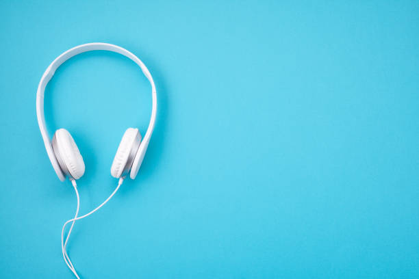 white earphones on blue background - headphones stock photos and pictures