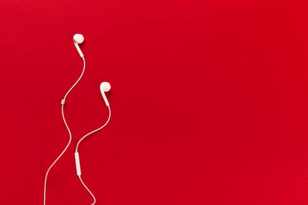 écouteurs blancs sur fond rouge - écouteurs intra auriculaires photos et images de collection