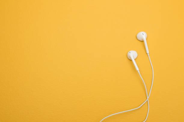 écouteurs blancs sur fond jaune, espace copie - écouteurs intra auriculaires photos et images de collection