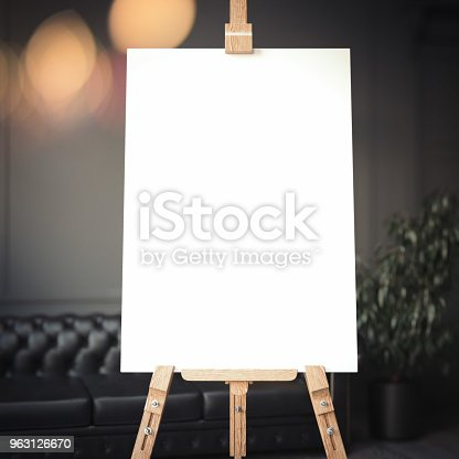 istock White easel stands next to dark wall and black sofa, 3d rendering 963126670